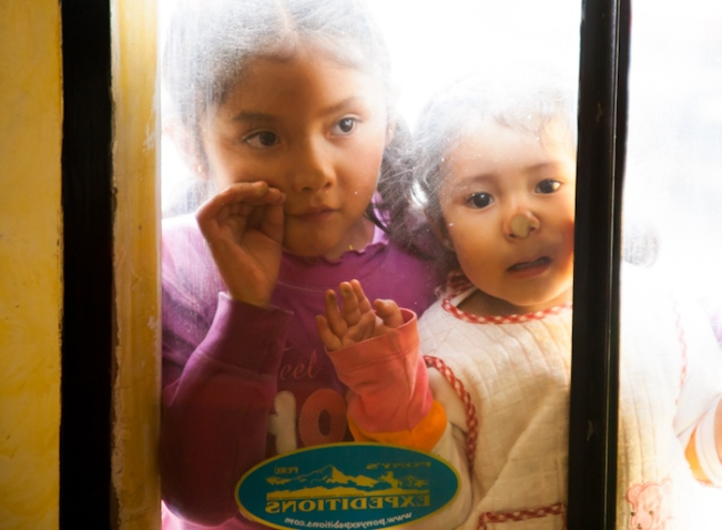 Peruvian children looking through glass